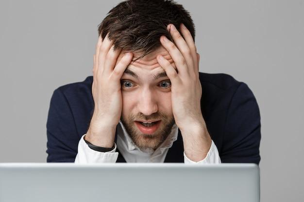 Concetto di affari - ritratto di uomo bello di affari stressante in abito shock guardando lavoro nel computer portatile. sfondo bianco.