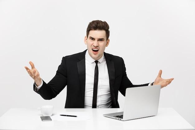Concetto di affari: ritratto dell'uomo d'affari arrabbiato di grido che si siede nell'ufficio isolato sopra fondo bianco.