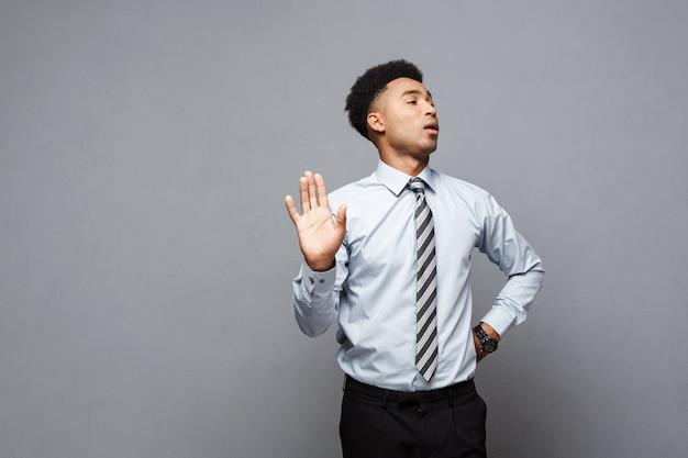 Concetto di affari - ritratto di uomo d'affari afroamericano sollecitato che mostra il fanale di arresto con la mano sul muro grigio.