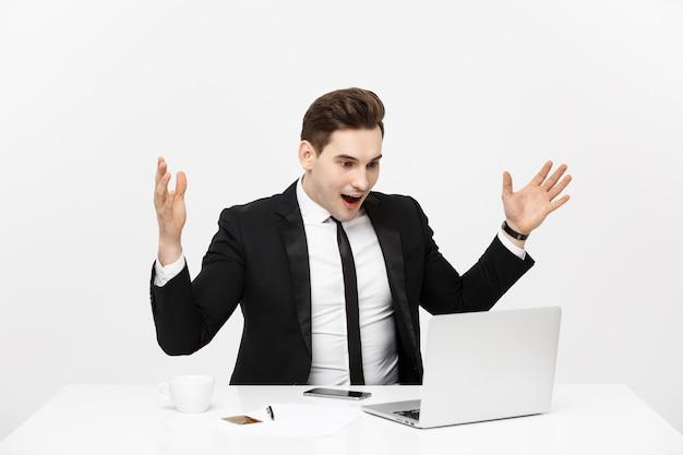 Il ritratto di concetto di affari ha sorpreso l'uomo d'affari in vestito nero che esamina la vista frontale della macchina fotografica isolata ...