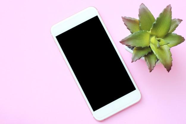 Smartphone e vasi da fiori di concetto aziendale posizionati sul rosa f
