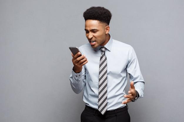 Concetto di affari - uomo d'affari afroamericano stressante che grida e che grida sul telefono cellulare.