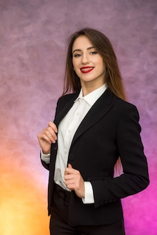 Concetto di affari. elegante imprenditrice in abito elegante in posa su sfondo astratto