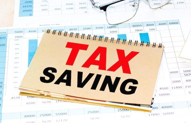Concetto di affari. testo risparmio fiscale foglio di carta per appunti, matite in background