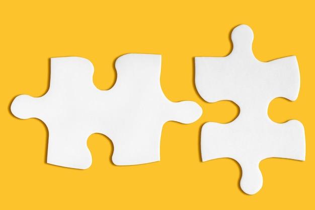 Concetto di affari. due pezzi di puzzle in bianco corrispondenti su giallo