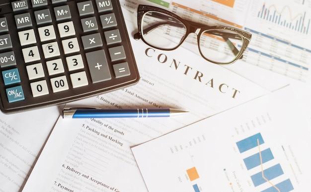Concetto di affari con bicchieri calcolatrice e matita sui documenti. grafici e grafici aziendali. contrarre