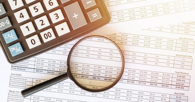 Concetto di affari con calcolatrice e lente di ingrandimento sui documenti