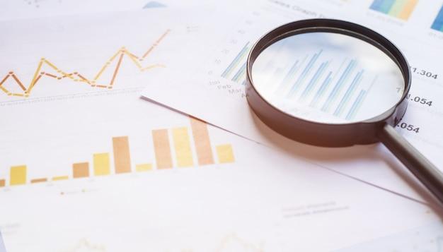 Concetto di affari con lente d'ingrandimento sui documenti. grafici e grafici aziendali