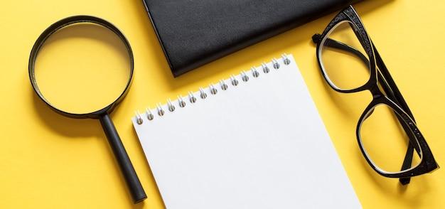Concetto di affari con notebook, lente d'ingrandimento e occhiali neri su giallo per il tuo design