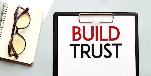 Concetto di affari con notebook e testo costruisci fiducia sul foglio di carta bianca