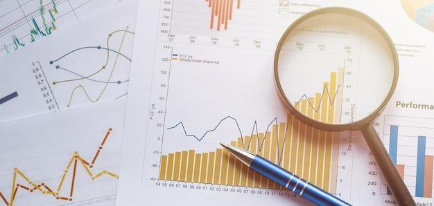 Concetto di affari con matita e lente di ingrandimento sui documenti. grafici e grafici aziendali