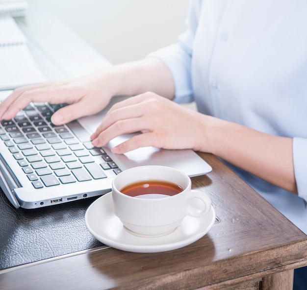 Concetto di affari. donna in maglietta blu digitando sul computer con caffè sul tavolo da ufficio, retroilluminazione, effetto abbagliamento del sole, primo piano, vista laterale, spazio di copia