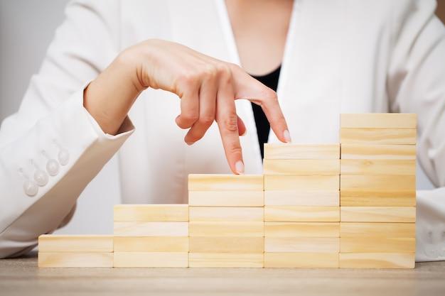 Il concetto di affari, alto vicino della donna compone i cubi di legno
