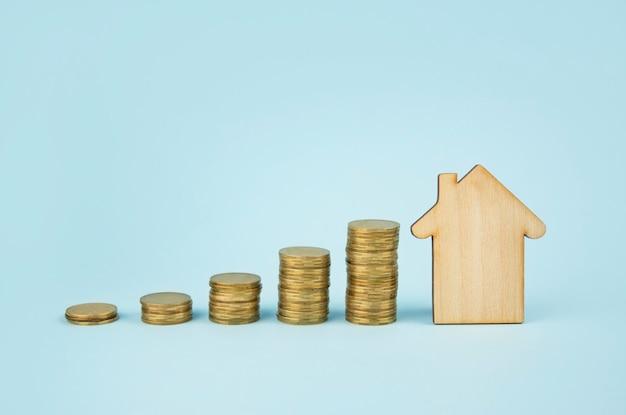 Concetto di affari. casa e monete in legno sull'azzurro