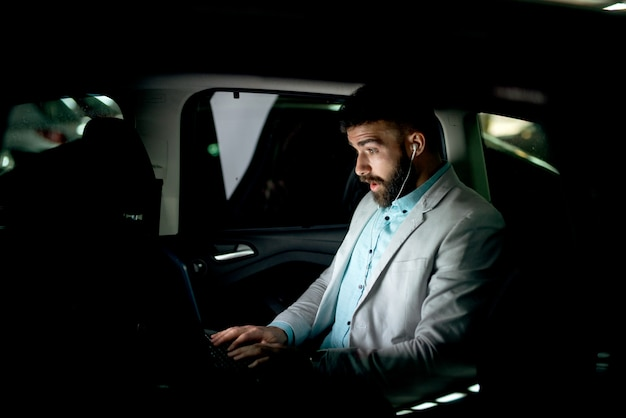 Il concetto di affari che lavora al computer portatile sorpreso l'uomo lavora in ritardo.