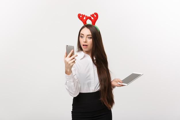 Concetto di affari - giovane donna caucasica di affari nel tema di natale che gioca il telefono del moblie con l'espressione facciale sorprendente.