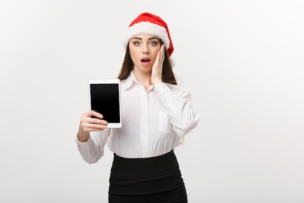 Concetto di affari - giovane donna caucasica di affari nel tema di natale che mostra la compressa digitale con l'espressione facciale sorprendente.