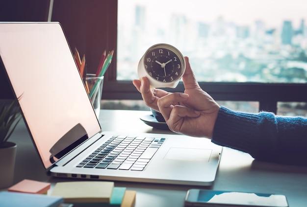 Concetti di affari con orologio della holding dell'uomo d'affari sul computer portatile del computer