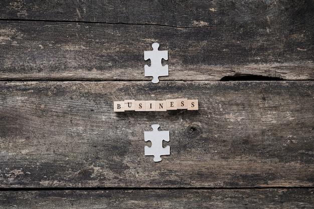 Immagine concettuale di affari - affari di parola ortografati sui blocchi di legno con i pezzi di puzzle sopra e sotto il segno