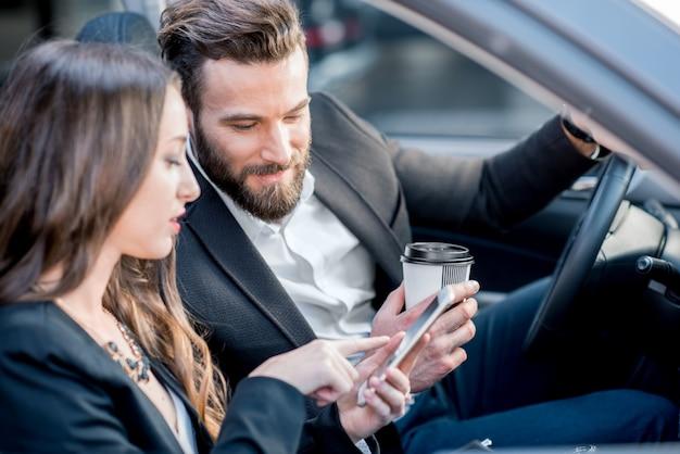 Coppia di affari che ha una conversazione mentre guida un'auto in città