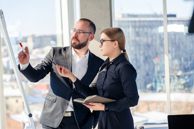 La coppia di affari sta discutendo qualcosa stando in piedi in ufficio. i partner commerciali stanno parlando di un nuovo progetto