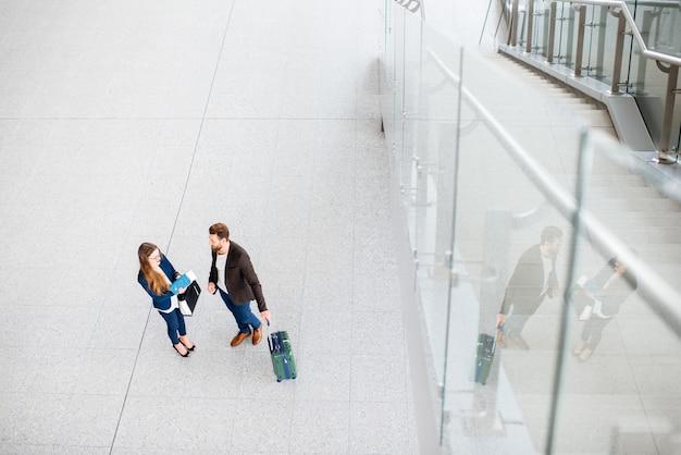 Coppia d'affari in piedi insieme al bagaglio in aeroporto. vista dall'alto, grandangolare con copia spazio