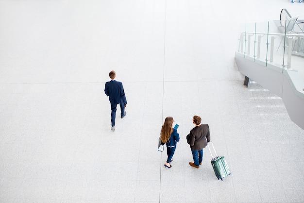 Coppie di affari che camminano con i bagagli all'aeroporto. vista dall'alto, grandangolare con copia spazio