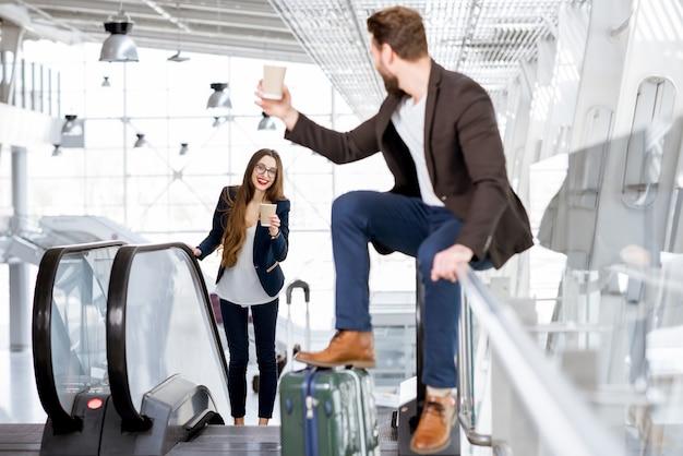 Coppia d'affari con caffè per andare in aeroporto. concetto di viaggio d'affari