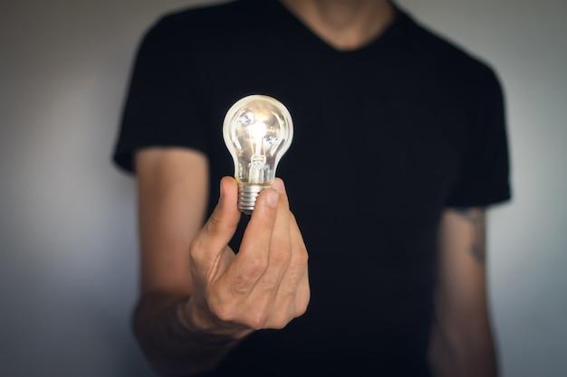 Concetto di creatività aziendale con l'uomo che tiene la lampadina.