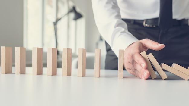 Concetto di gestione della crisi aziendale - mediatore aziendale che ferma la caduta dei domini con la mano.