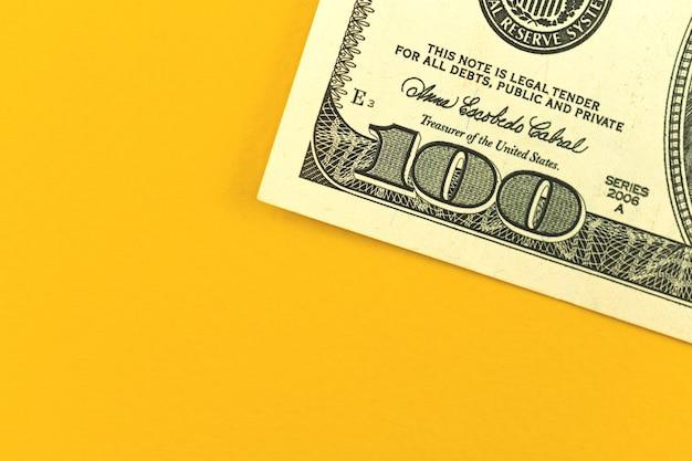 Concetto di deposito aziendale, tavolo da ufficio con denaro, primo piano di una banconota da 100 dollari usa su sfondo giallo, foto vista dall'alto