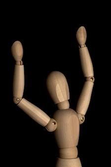 Concetto di business e design - manichino in legno con gesto del braccio aperto isolato su sfondo nero