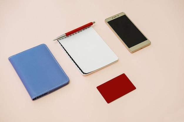Scrivania da lavoro piatta con portafoglio, blocco note, smartphone e carta di credito.