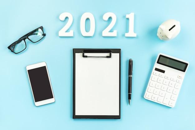 Ufficio scrivania aziendale con smart phone e calcolatrice su blu, 2021 concetto finanziario con spazio di copia
