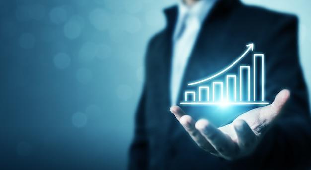 Sviluppo del business verso il successo e un concetto di crescita crescente. grafico della tenuta dell'uomo d'affari e aumento della freccia