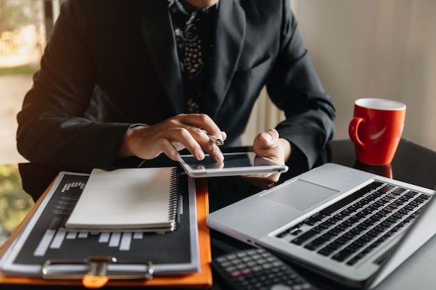 Documenti aziendali sul tavolo dell'ufficio con smartphone e tablet digitale e grafico finanziario e uomo che lavora