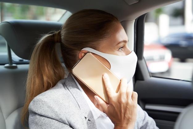 Affari durante il coronavirus donna d'affari che indossa una maschera protettiva che parla al telefono cellulare