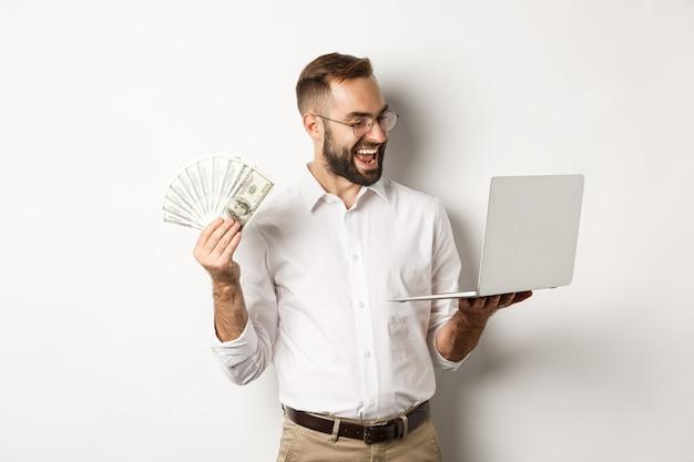 Commercio e commercio elettronico. uomo d'affari soddisfatto che fa lavoro sul laptop e tiene in mano soldi, sorride felice, in piedi su sfondo bianco