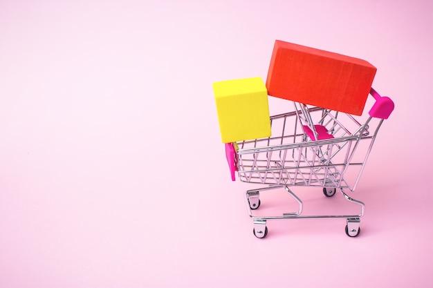 Concetto di e-commerce aziendale primo piano carrello della spesa in metallo giocattolo con scatola gialla rossa all'interno su rosa