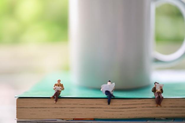 Concetto di business, istruzione, informazione e distanziamento sociale. tre figure in miniatura di uomo d'affari seduti e leggendo il libro e il giornale sulla pila di libri con tazza bianca tazza di caffè caldo.