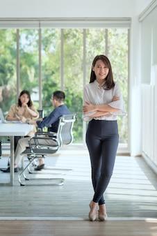 L'impiegato aziendale gode e felice di lavorare nell'ufficio dell'azienda con un atteggiamento positivo.