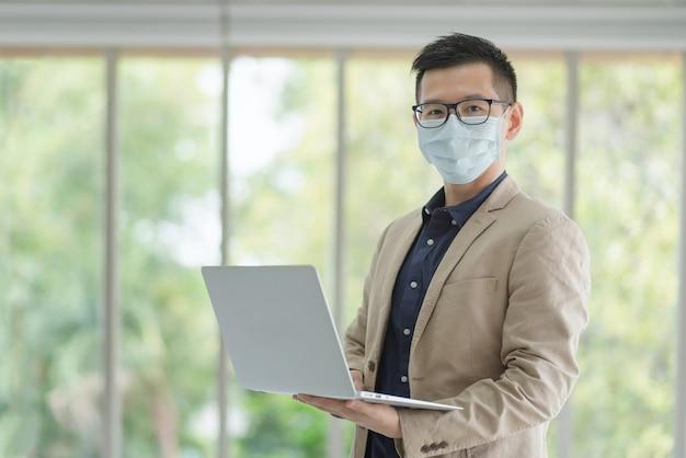 I dipendenti aziendali che indossano una maschera durante il lavoro in ufficio per mantenere l'igiene seguono la politica aziendale. preventivo durante il periodo di epidemia da coronavirus o covid19.