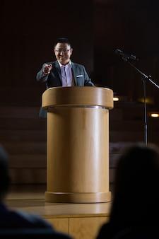 Esecutivo di affari che indica mentre dà un discorso al centro congressi
