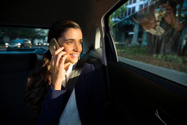 Dirigente aziendale parlando al telefono cellulare in auto
