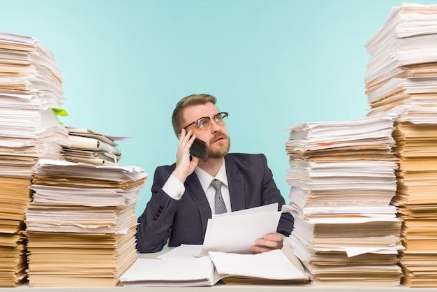 Dirigente aziendale parlando al telefono che lavora in ufficio e pile di scartoffie