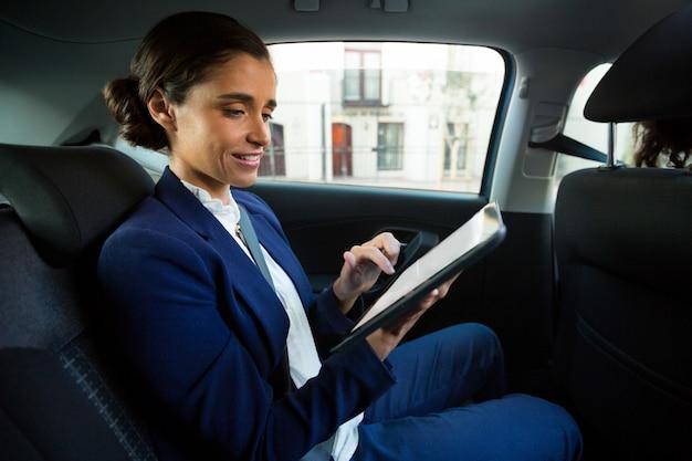 Dirigente aziendale utilizzando la tavoletta digitale in auto