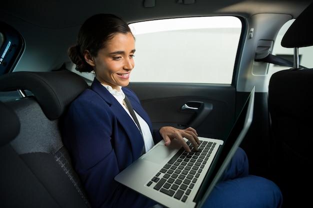 Dirigente aziendale utilizzando laptop in auto