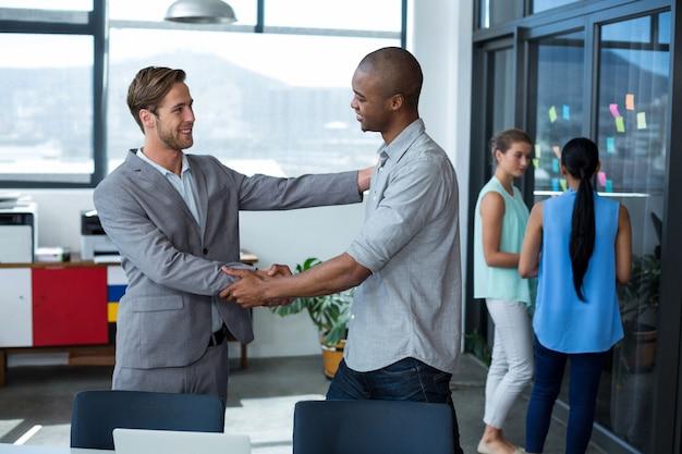 Uomini d'affari che stringono le mani in ufficio