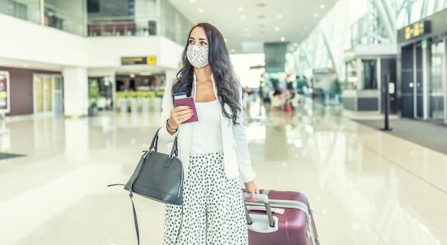 La viaggiatrice d'affari in maschera facciale sta cercando un cancello adeguato all'aeroporto che tira un bagaglio.