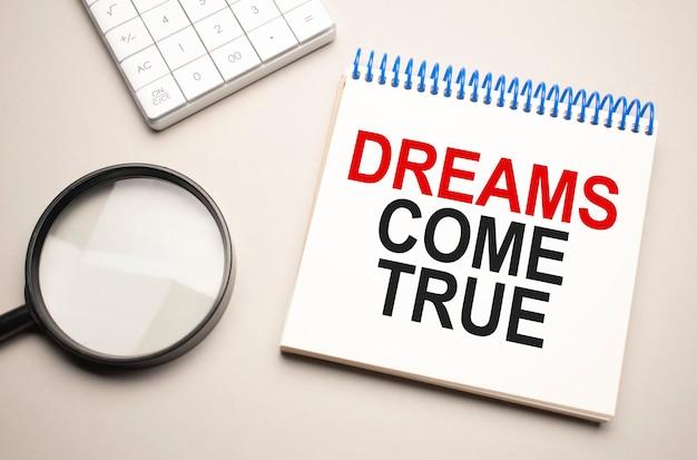 Concetto di affari e finanza. sul tavolo c'è una lente d'ingrandimento, una calcolatrice e un quaderno con la scritta - dreams come true